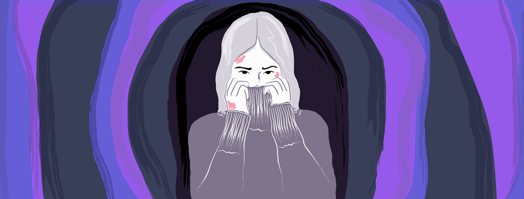 Woman is in the middle of a cave-like tunnel, covering her face with her turtleneck sweater.