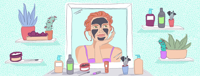 A woman is gazing into the mirror, wearing a charcoal face mask, and contemplating the next product to use. Her products are scattered about her vanity.