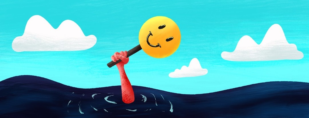 person sinking in water while holding up a mask with a smiley face