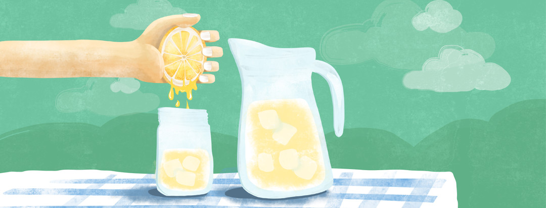 A hand squeezes a lemon over a glass on a picnic table.