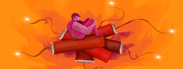 Male adult sits on top of a pile of dynamite with flames in the background.