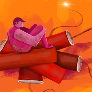 A man hugs his knees to his chest sadly while sitting atop a stack of lit dynamite.