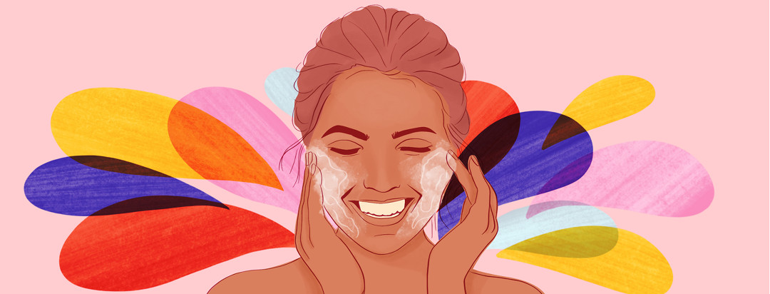 A woman rubs face wash into her cheeks, smiling, while multicolored splashes happen in the background.