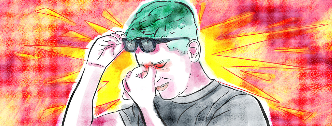 A man removes his glasses and grabs at his itching eyes that appear red and blotchy.