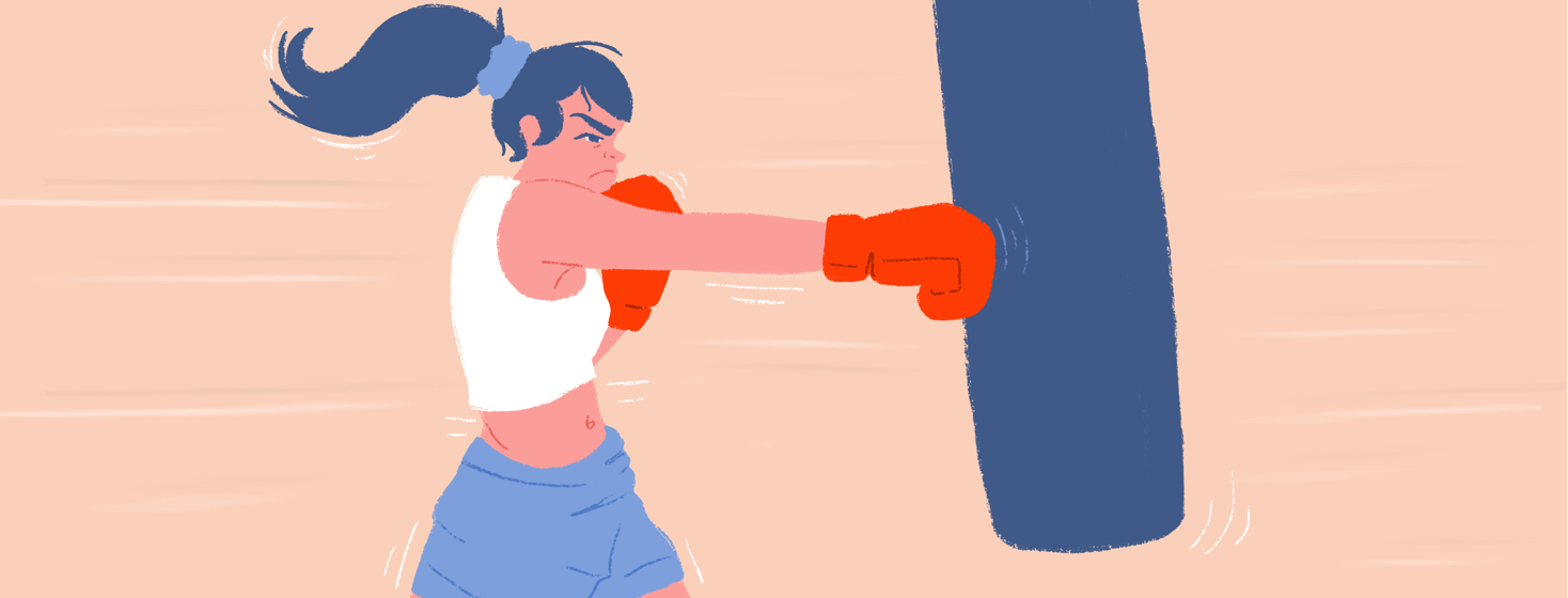 A female boxer spiritedly punches a punching bag with boxing gloves.