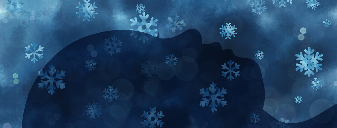 A facial profile silhouetted with snowflakes falling gently down upon it.