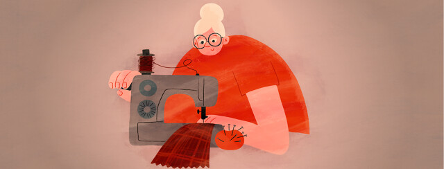 A woman sits at her sewing machine.