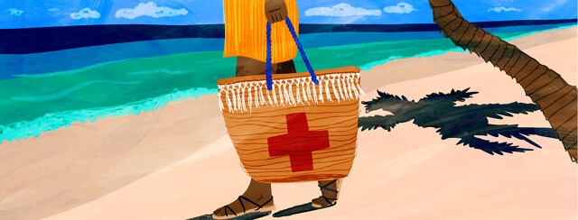 A woman walks down the beach holding a beach bag with a red cross on it.