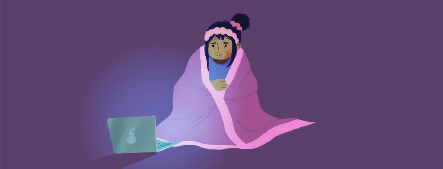 Adult female covered in a blanket is watching a tv show on her laptop and finding comfort in it. Relaxation, television, video streaming. POC